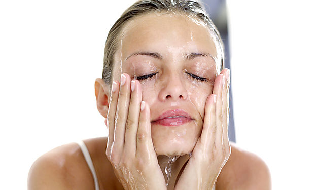 portrait of a woman washing her face with water