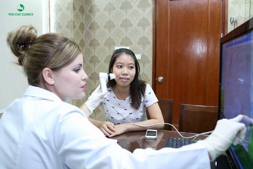 Chuyên gia Thu Cúc Clinics đang thăm khám và tư vấn trị mụn cho khách hàng.